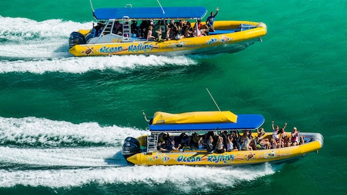 Two Ocean Rafting boats full of people motor out on the ocean
