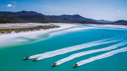 Beautiful aerial view of the ocean with four raft boats riding across.