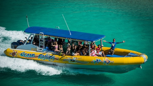 View of yellow Ocean Rafting boat with several people aboard posing for camera.