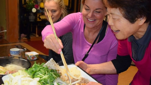 A woman grabbing food off a plate with chop sticks