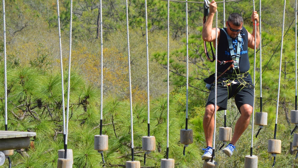 Show item 5 of 5. Man crosses a suspended obstacle course