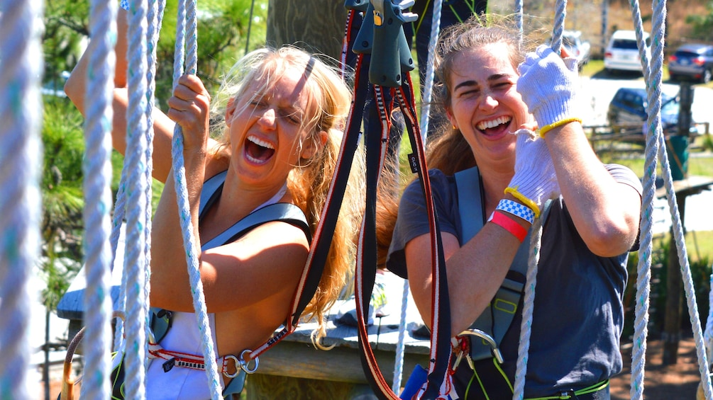 Show item 2 of 5. Two women laughing at a ropes obstacle course