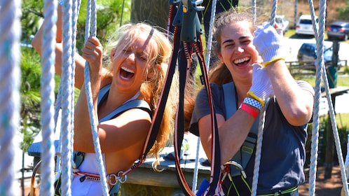 Two women laughing at a ropes obstacle course