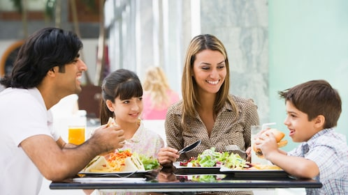 Family eats food at a table in public