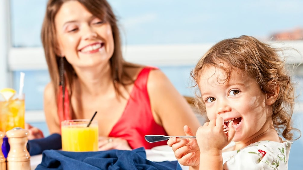 Little girl eats breakfast with mother at table