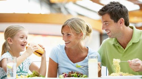 Girl eats sandwich while mother eats salad and father eats plain noodles
