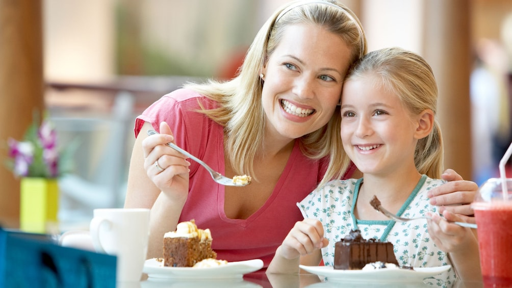 Woman and daughter eat cake.