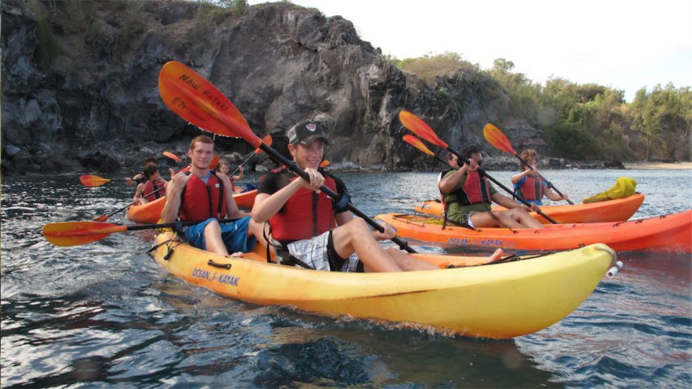 Group of kayakers paddle from the shore in Maui