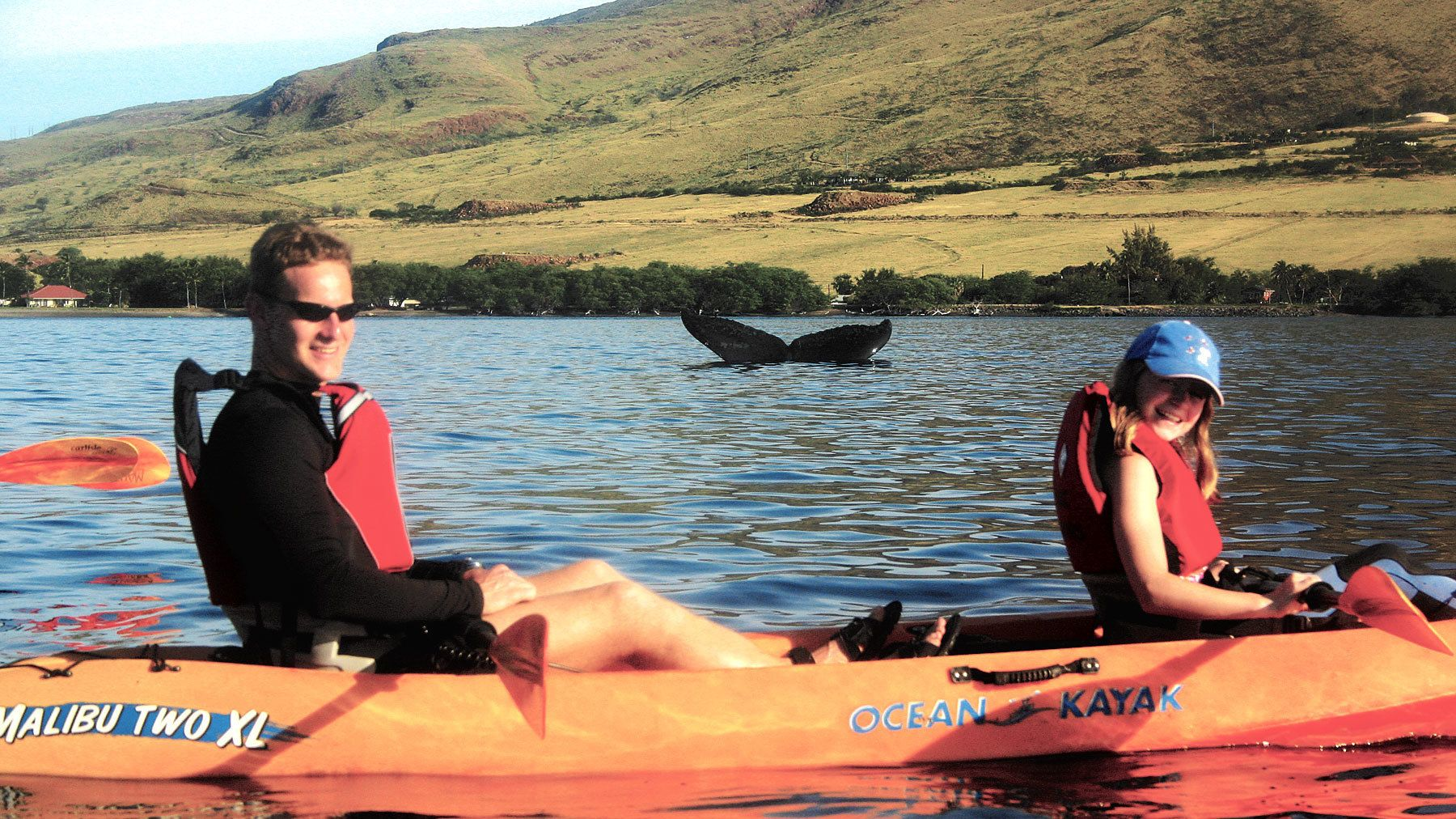 Father and daughter have picture taken with whale tail in background in Maui