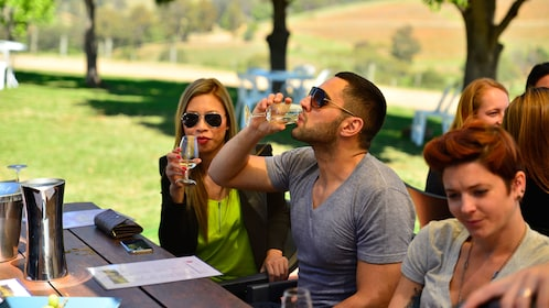 Couple tasting wine at a communal table at a winery in Hunter Valley