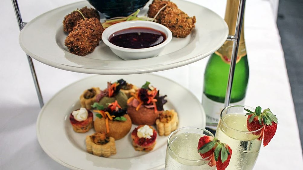 Small appetizers on white plates with bottle of champagne.