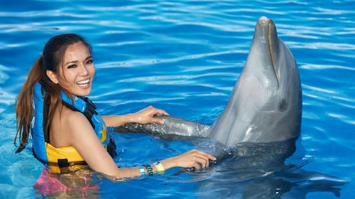 woman holding a dolphin's flippers
