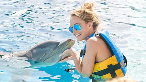 woman petting an emerged dolphin