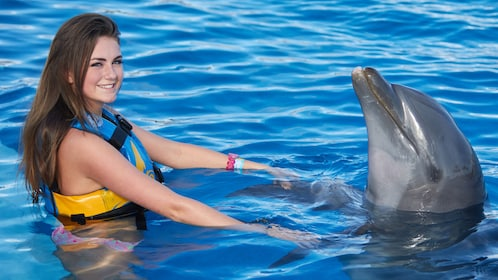 A woman holds on to a Dolphins fins