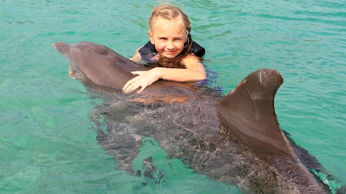 Little girl holds onto dolphin during encounter tour in Ochos Rios