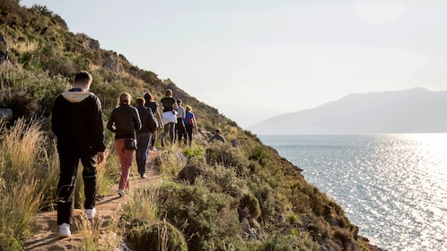Hikers walk along a path next overlooking the coast of Greece,