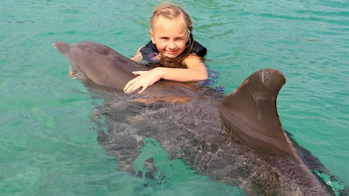 Little girl holds onto dolphin at dolphin encounter in Ochos Rios