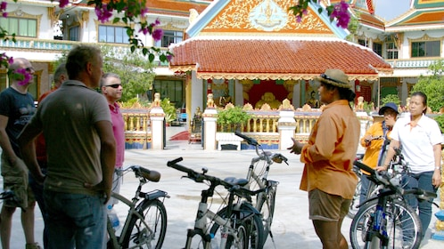 Bike tour group stops and is instructed about the local culture in Bangkok