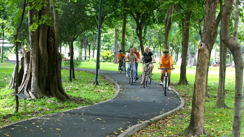 Group of Bicyclists ride down a bike path in a park in Bangkok