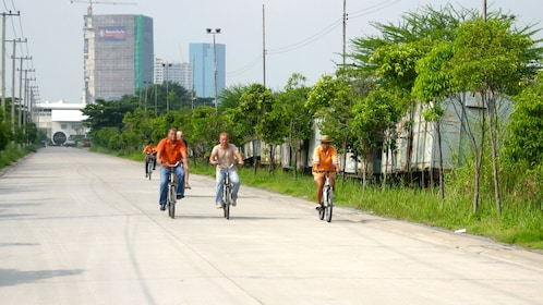 Bicycle tour group rides down a road in the rural area of Bangkok