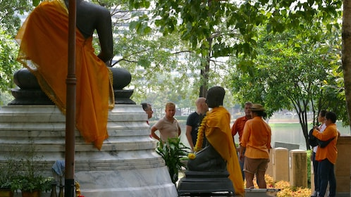 Tour group passes a group of Buddhist statues that are wearing orange robes