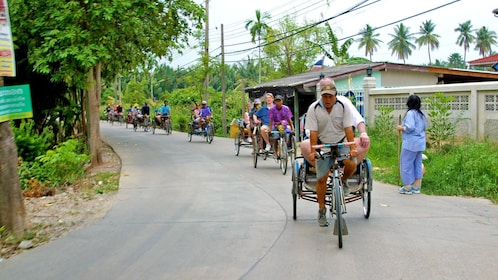 group of passengers on rickshaws on a small village road in Bangkok