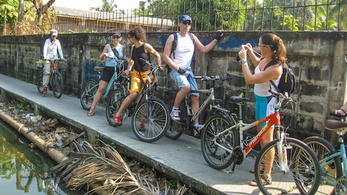 Group of cyclists observing river in Bangkok.
