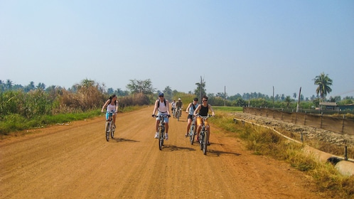 Group of cyclists riding bikes on dirt road.