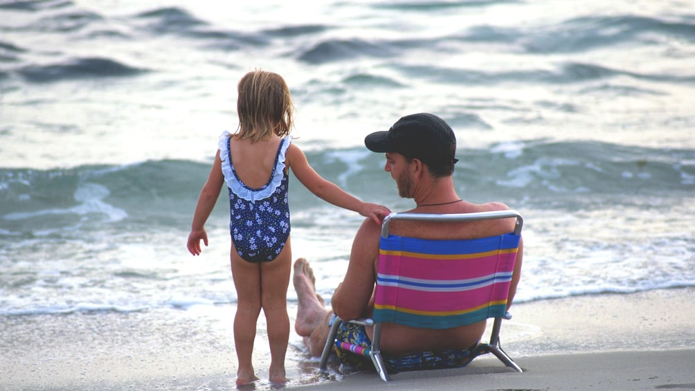 Show item 3 of 4. Father and daughter on beach chairs relaxing on the Maui coast