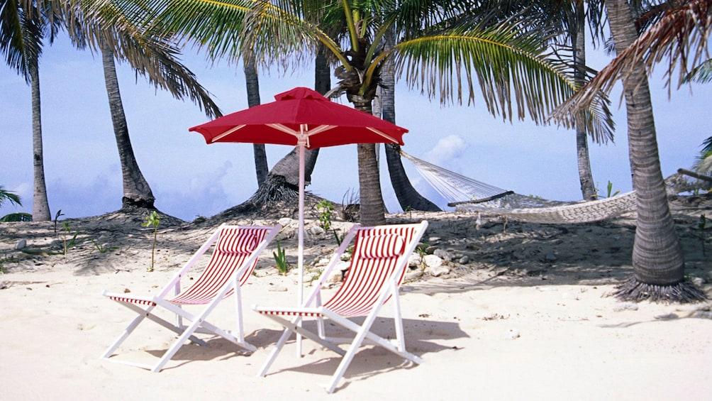 Show item 4 of 4. Beach chairs and umbrella on the Maui coast