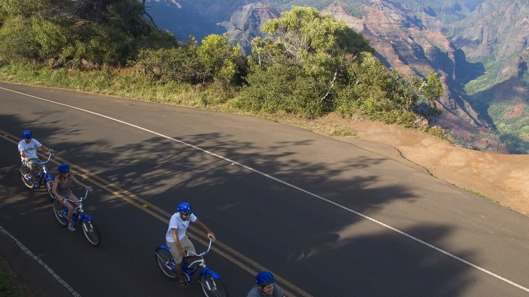 four people on bikes riding down street in Kauai
