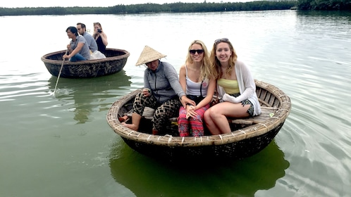 Two disc shaped boats with three people in each one in Vietnam