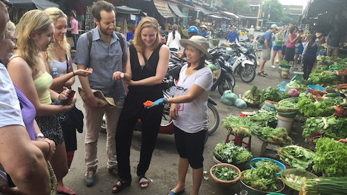 A guide holds out produce for a cooking class in a street market in Hoi An