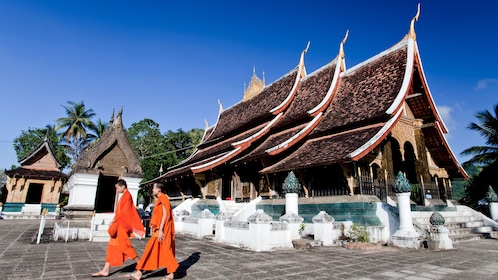 Two monks walk past an ornate pagoda in Laos