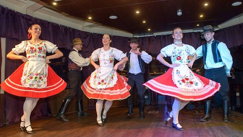 Six dancers in local dress dance for a dinner cruise in Budapest