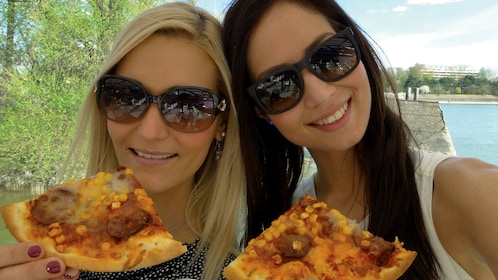 Pair of women taking a selfie with slices of pizza