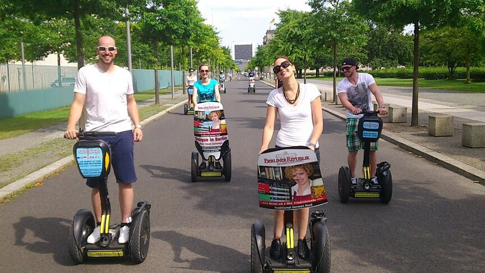 People ride on Segways in the streets of Berlin