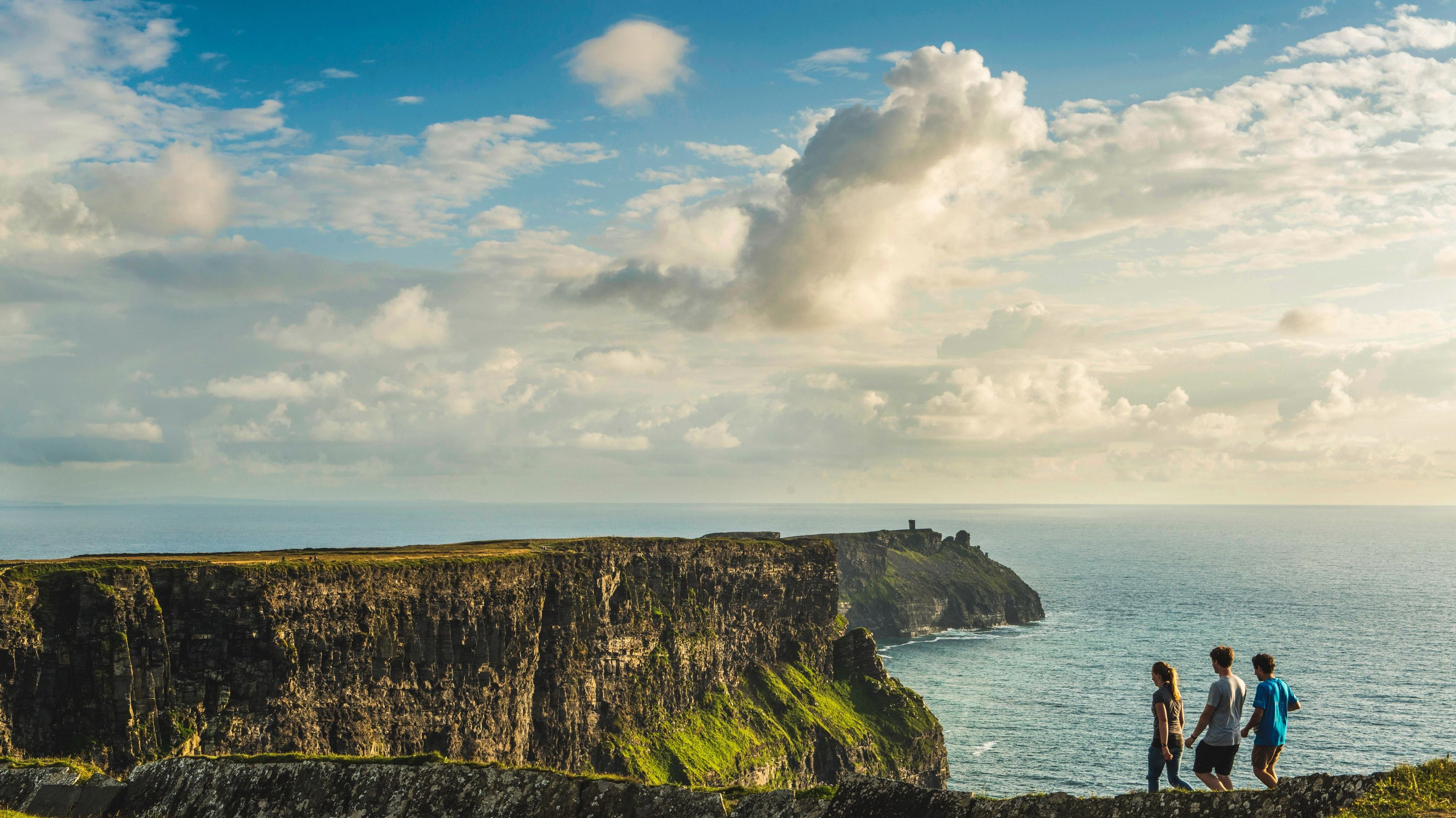 Beautiful view of Cliffs of Moher with hikers seen walking nearby.
