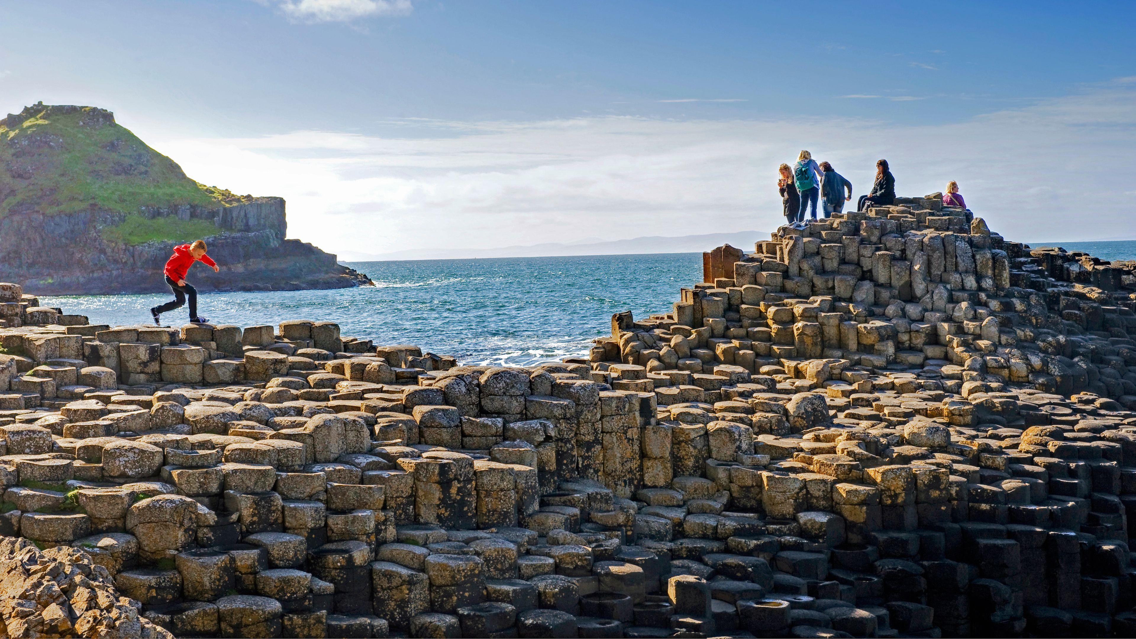 people walking on rock formations in ireland