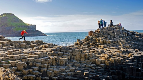people walking on rock formations in ireland