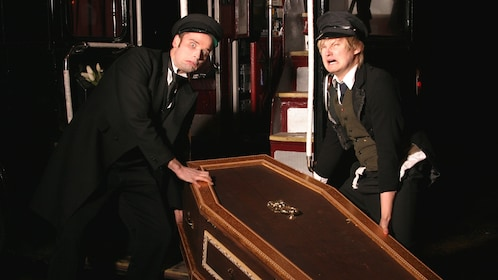 Tour actors in costume lifting heavy coffin.