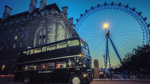 Angled view of tour bus driving down London street at night.