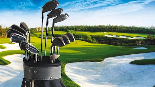 Close up of golf clubs with view of golf course in the distance.