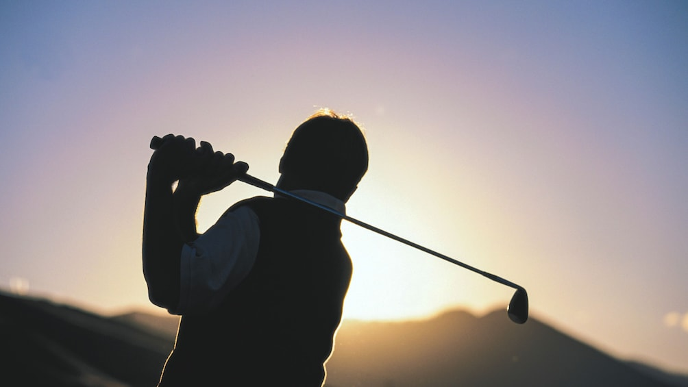 Show item 5 of 5. Silhouette of golfer at sunset.