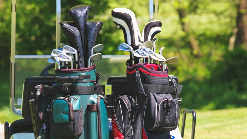 Show item 4 of 5. Close up of several golf clubs in bags.
