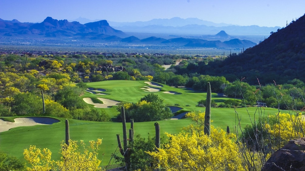 Show item 3 of 5. Beautiful landscape view of golf course with mountains in the distance.