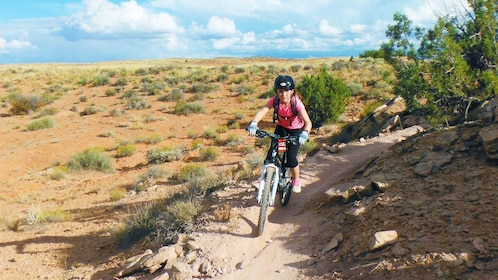 girl riding bike through a narrow trail in Green River