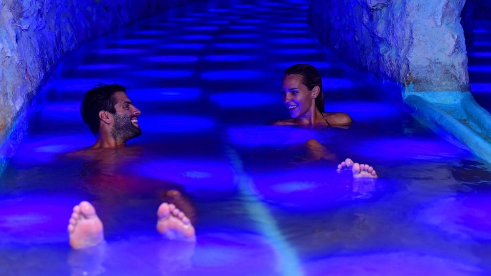 Lataa valokuva 3 kautta 10. Two people float in blue water in a lagoon