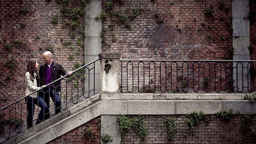 Couple standing on a staircase to an ivy covered building in Barcelona