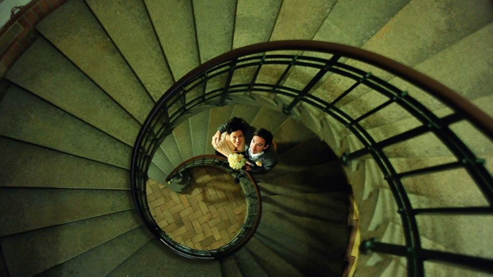 Indlæs billede 1 af 5. Looking down at a bride and groom at the bottom of a spiral staircase in Coppenhagen
